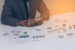 Χέρια επιχειρηματιών που λειτουργούν με ένα smartphone στο άσπρο επιτραπέζιο υπόβαθρο Στοκ φωτογραφία με δικαίωμα ελεύθερης χρήσης