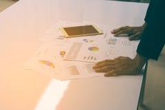 Χέρια επιχειρηματιών που λειτουργούν με μια ταμπλέτα στο άσπρο επιτραπέζιο υπόβαθρο Στοκ Εικόνα