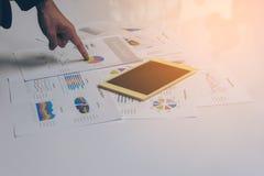 Χέρια επιχειρηματιών που λειτουργούν με μια ταμπλέτα στο άσπρο επιτραπέζιο υπόβαθρο Στοκ Εικόνες
