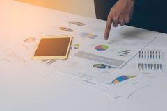 Χέρια επιχειρηματιών που λειτουργούν με μια ταμπλέτα στο άσπρο επιτραπέζιο υπόβαθρο Στοκ Φωτογραφίες