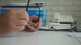 Χέρια επιχειρηματιών που κάνουν τις ανήσυχες χειρονομίες με τα γυαλιά σε μια επιχειρησιακή συνεδρίαση απόθεμα βίντεο