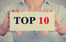 Χέρια επιχειρηματιών που κρατούν το σημάδι καρτών με top 10 το μήνυμα κειμένου Στοκ εικόνες με δικαίωμα ελεύθερης χρήσης