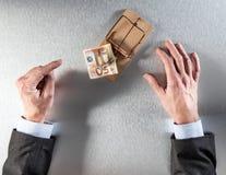 Χέρια επιχειρηματιών που παρουσιάζουν δισταγμό που αντιμετωπίζει τα ευρο- χρήματα στην παγίδα ποντικιών Στοκ Φωτογραφίες
