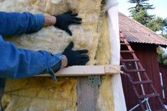 Χέρια εργαζομένων στο υλικό rockwool σπιτιών insulatiom Στοκ φωτογραφία με δικαίωμα ελεύθερης χρήσης