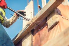 Χέρια εργατών οικοδομών που εξασφαλίζουν τους ξύλινους πίνακες με τη ράβδο καλωδίων Στοκ φωτογραφία με δικαίωμα ελεύθερης χρήσης