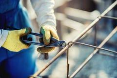 χέρια εργατών οικοδομών που εξασφαλίζουν τους φραγμούς χάλυβα με τη ράβδο καλωδίων για την ενίσχυση του σκυροδέματος Στοκ εικόνα με δικαίωμα ελεύθερης χρήσης