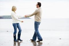 χέρια ζευγών παραλιών που κρατούν το περπάτημα χαμόγελου στοκ φωτογραφίες