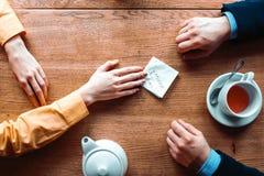Χέρια ζεύγους με τη σημείωση αγάπης για το ξύλινο υπόβαθρο Στοκ φωτογραφία με δικαίωμα ελεύθερης χρήσης