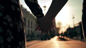 Χέρια ζεύγους που κρατούν το ένα το άλλο στο φως ηλιοβασιλέματος οδών πόλεων με την όμορφη φλόγα φακών φιλμ μικρού μήκους