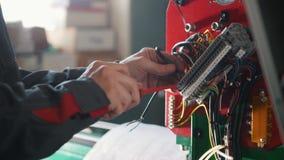 Χέρια ηλεκτρολόγων ` s που εγκαθιστούν το ενεργειακό σύστημα στη βιομηχανία μηχανημάτων φιλμ μικρού μήκους