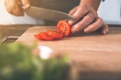Χέρια ηλικιωμένων γυναικών που κόβουν την ντομάτα στον ξύλινο πίνακα Στοκ εικόνες με δικαίωμα ελεύθερης χρήσης
