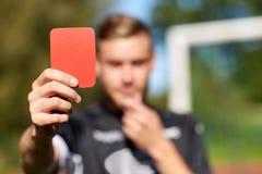 Χέρια διαιτητών με την κόκκινη κάρτα στο αγωνιστικό χώρο ποδοσφαίρου Στοκ Φωτογραφίες