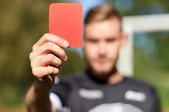 Χέρια διαιτητών με την κόκκινη κάρτα στο αγωνιστικό χώρο ποδοσφαίρου Στοκ Εικόνες