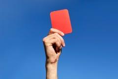 Χέρια διαιτητών με την κόκκινη κάρτα στο αγωνιστικό χώρο ποδοσφαίρου Στοκ φωτογραφία με δικαίωμα ελεύθερης χρήσης