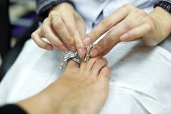 Χέρια, καθαρίζοντας καρφιά δάχτυλων του ποδιού των γυναικών Στοκ Εικόνες