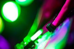 Χέρια και jockey δίσκων δάχτυλων στα παιχνίδια του DJ περιστροφικών πλακών στο νυχτερινό κέντρο διασκέδασης Στοκ εικόνα με δικαίωμα ελεύθερης χρήσης