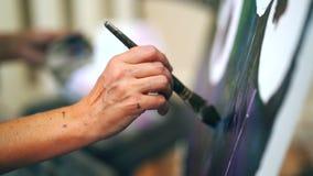 Χέρια καλλιτεχνών γυναίκας που επισύρουν την προσοχή την εικόνα με τα ελαιοχρώματα στον καμβά απόθεμα βίντεο