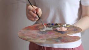 Χέρια καλλιτεχνών με τη βούρτσα που αναμιγνύει τα χρώματα στην παλέτα κοντά επάνω Τέχνη, δημιουργικότητα, χόμπι φιλμ μικρού μήκους