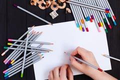 Χέρια καλλιτεχνών που κρατούν το μολύβι χρώματος και το κενό φύλλο του εγγράφου Στοκ Εικόνες
