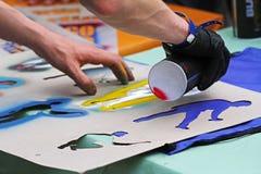 Χέρια καλλιτεχνών ` s γκράφιτι που επισύρουν την προσοχή τον αριθμό στο ύφασμα που χρησιμοποιεί ένα διάτρητο Στοκ Φωτογραφία