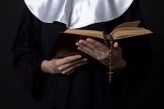 Χέρια καλογριών που κρατούν το βιβλίο Βίβλων πέρα από το γκρι Στοκ φωτογραφία με δικαίωμα ελεύθερης χρήσης