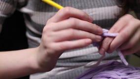 Χέρια κινηματογραφήσεων σε πρώτο πλάνο με το πλέξιμο των βελόνων Η όμορφη γυναίκα πλέκει απόθεμα βίντεο