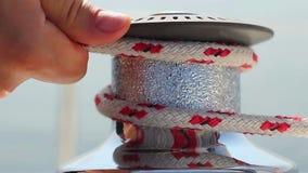 Χέρια κινηματογραφήσεων σε πρώτο πλάνο που εξασφαλίζουν το σχοινί στη βάρκα Ιστιοπλοϊκός, προετοιμαμένος να πλεύσει απόθεμα βίντεο