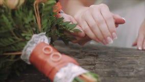 Χέρια κινηματογραφήσεων σε πρώτο πλάνο της νύφης και του νεόνυμφου και δαχτυλίδια στη γαμήλια ανθοδέσμη έννοια γάμου φιλμ μικρού μήκους