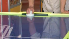 Χέρια κινηματογραφήσεων σε πρώτο πλάνο του παιχνιδιού ατόμων σε ένα χόκεϋ αέρα φιλμ μικρού μήκους