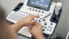 Χέρια κινηματογραφήσεων σε πρώτο πλάνο των εργασιών γιατρών για τον ανιχνευτή υπερήχου Ιατρικός ειδικός εξοπλισμός χρήσης εργαζομ απόθεμα βίντεο