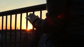 Χέρια κινηματογραφήσεων σε πρώτο πλάνο που χρησιμοποιώντας app στο έξυπνο τηλέφωνο στο ηλιοβασίλεμα ρετηρέ στεγών μπαλκονιών φιλμ μικρού μήκους