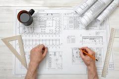 Χέρια κινηματογραφήσεων σε πρώτο πλάνο του αρχιτέκτονα που λειτουργούν με το μολύβι σε ένα σχέδιο Στοκ Εικόνα