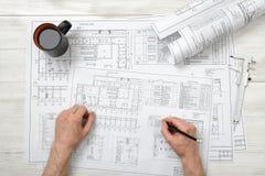 Χέρια κινηματογραφήσεων σε πρώτο πλάνο του αρχιτέκτονα που λειτουργούν με το μολύβι σε ένα σχέδιο Στοκ εικόνες με δικαίωμα ελεύθερης χρήσης
