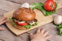 Χέρια κοριτσιών κοντά burger μανιταριών με το τυρί και τις ντομάτες, ακατέργαστα champignons και το μαρούλι, τεμαχίζοντας πίνακας στοκ εικόνες με δικαίωμα ελεύθερης χρήσης