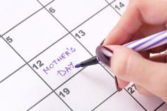 Χέρια κοριτσιών με αισθητή την πορφύρα μάνδρα που γράφει στην ημέρα μητέρων ημερολογιακών λέξεων στοκ φωτογραφίες