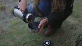 Χέρια κοριτσιών με τα thermos και το καυτό τσάι φλυτζανιών φιλμ μικρού μήκους