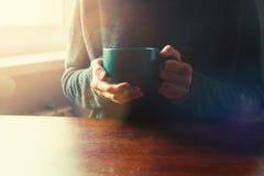 Χέρια κοριτσιών με το φλιτζάνι του καφέ ή το τσάι Στοκ Εικόνα