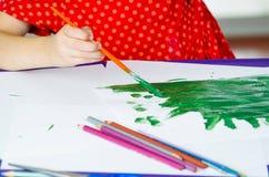 Χέρια κοριτσιών που κρατούν τη ζωγραφική βουρτσών χρωμάτων Στοκ εικόνες με δικαίωμα ελεύθερης χρήσης