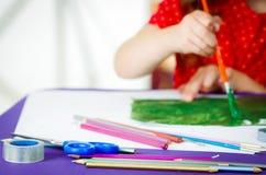Χέρια κοριτσιών που κρατούν τη ζωγραφική βουρτσών χρωμάτων Στοκ Εικόνες