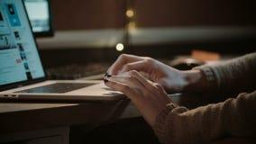 Χέρια κοριτσιών σε ένα lap-top touchpad Κινηματογράφηση σε πρώτο πλάνο Γυναίκα στο πουλόβερ που κάνει σερφ τον Ιστό στο σκοτάδι σ απόθεμα βίντεο