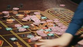 Χέρια κρουπιερών που αφαιρούν τα τσιπ χαρτοπαικτικών λεσχών από το παιχνίδι του πίνακα Πίνακας ρουλετών χαρτοπαικτικών λεσχών φιλμ μικρού μήκους