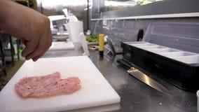Χέρια μαγείρων που καρυκεύουν το κρέας κοτόπουλου με τα διαφορετικά χορτάρια