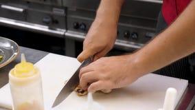 Χέρια μαγείρων που κόβουν ένα κομμάτι του τηγανισμένου κρέατος στηθών κοτόπουλου φιλμ μικρού μήκους