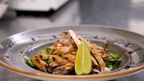 Χέρια μαγείρων που τοποθετούν ένα κομμάτι του ασβέστη στη σαλάτα αβοκάντο με το ψημένο στη σχάρα κρέας απόθεμα βίντεο