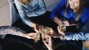 Χέρια με τα γυαλιά του κουδουνίσματος κρασιού σε έναν μαύρο πίνακα με την αντανάκλαση Ομάδα φίλων σε ένα εστιατόριο που γιορτάζει απόθεμα βίντεο