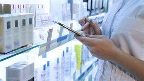 Χέρια με την ταμπλέτα στο υπόβαθρο του φαρμακείου απόθεμα βίντεο