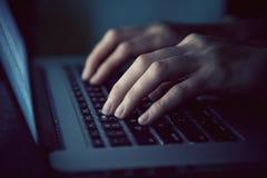 Χέρια με τη δακτυλογράφηση lap-top τη νύχτα Στοκ Φωτογραφίες