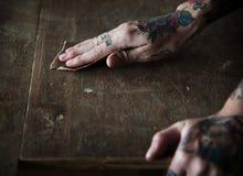 Χέρια με τη δερματοστιξία που χρησιμοποιεί το γυαλόχαρτο σε ένα ξύλο στοκ εικόνα με δικαίωμα ελεύθερης χρήσης