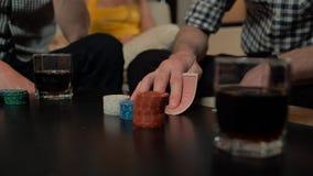 Χέρια με τις κάρτες και τα τσιπ παιχνιδιού πόκερ απόθεμα βίντεο