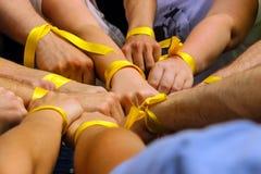 Χέρια με τις κίτρινες κορδέλλες από κοινού Στοκ εικόνα με δικαίωμα ελεύθερης χρήσης